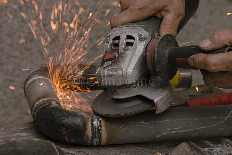 Arbetaren klipper ett metallrör med hjälp av det slipande hjälpmedlet arkivbilder
