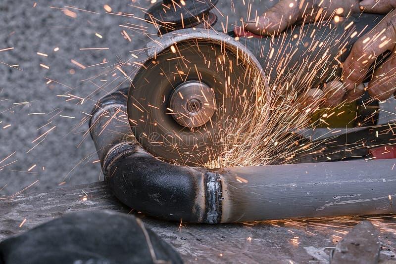 Arbetaren klipper ett metallrör med hjälp av det slipande hjälpmedlet royaltyfri foto