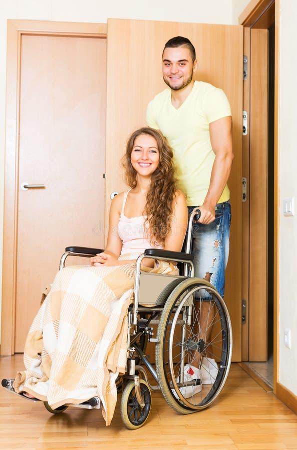 Arbetaren kom med personen i rullstol arkivbilder