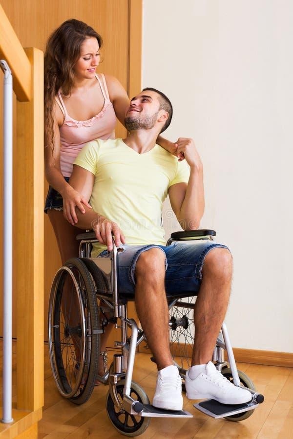 Arbetaren kom med personen i rullstol royaltyfria foton