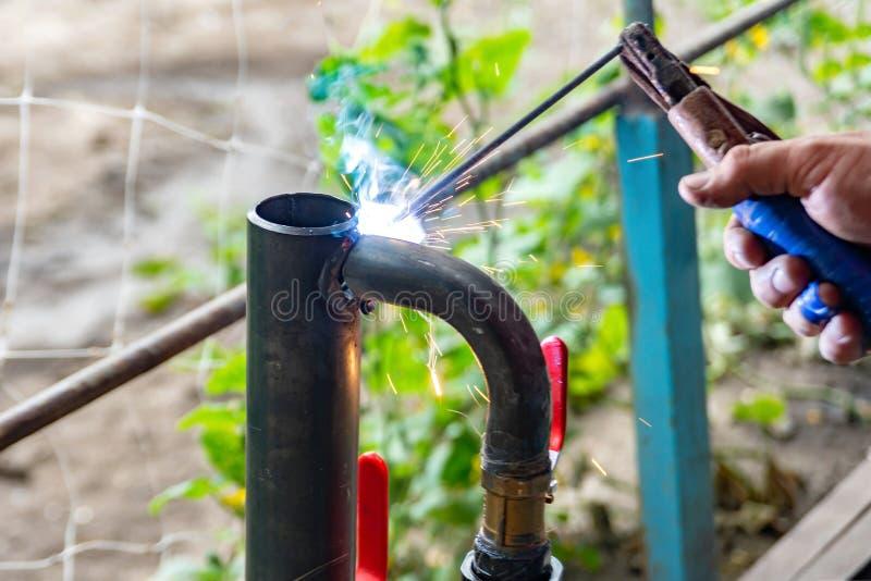 Arbetaren lagar mat det värma röret som svetsar skarven Förbereda sig för vinteruppvärmning arkivbild