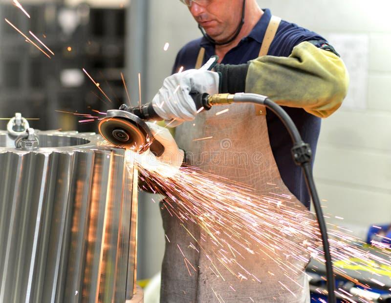 Arbetaren med en malande maskin bearbetar ett kugghjulhjul - producti arkivbild