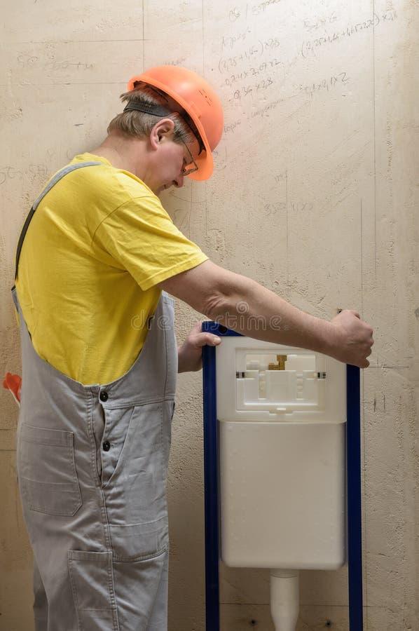 Arbetaren monterar en inbyggd toalettbehållare arkivbilder