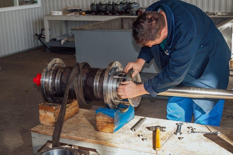 Arbetaren monterar maskindelen i en fabrik arkivfoto