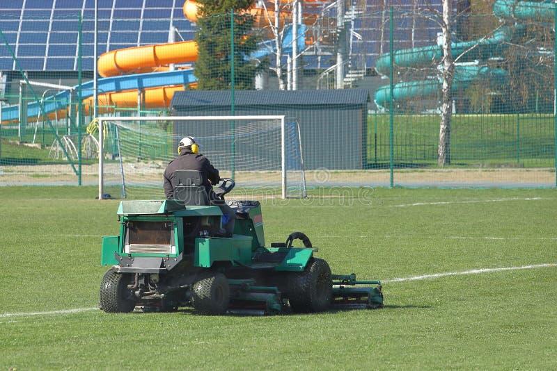 Arbetaren på en stor grön gräsklippare mejar gräset på fotbollfältet Landskapdesign och underhåll av grönområden av arkivfoton