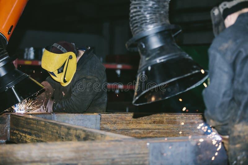 Arbetaren på fabriken i hjälmen är av järn i den svetsande pren royaltyfri fotografi