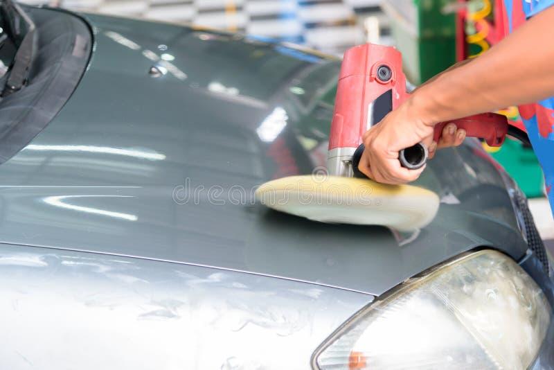 Arbetaren polerar bilen med bilen royaltyfri bild