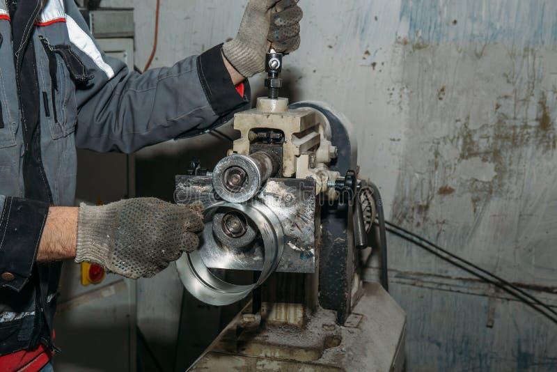 Arbetaren räcker tätt upp och att arbeta med metallutrustning i industriell fabrik arkivfoton
