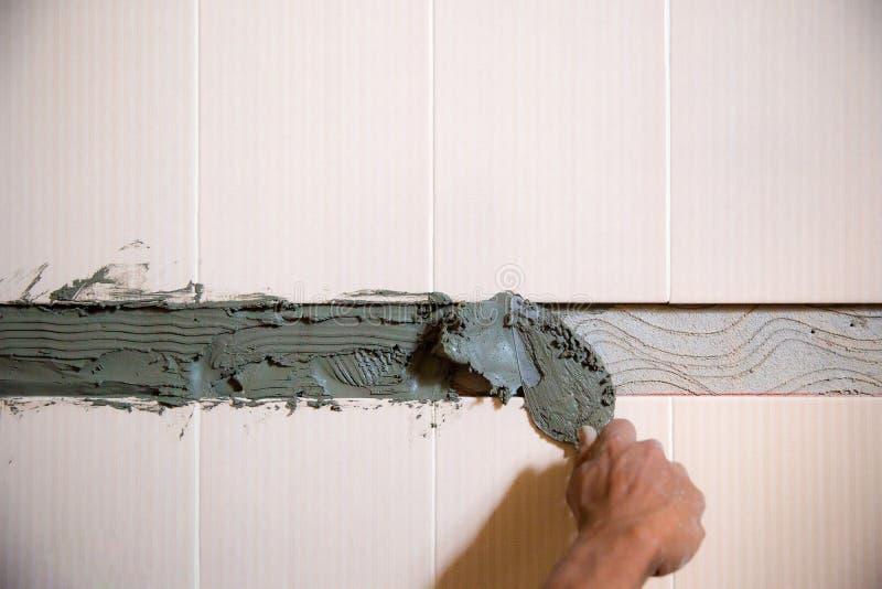 Arbetaren rappar cement på väggen mortelmurbrukprocess arkivbilder