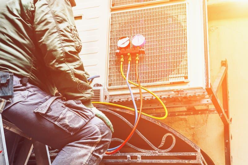 Arbetaren reparerar eller förhindrar luftkonditioneringsapparaten på väggen, betingande reparationsbegrepp för luft royaltyfri bild