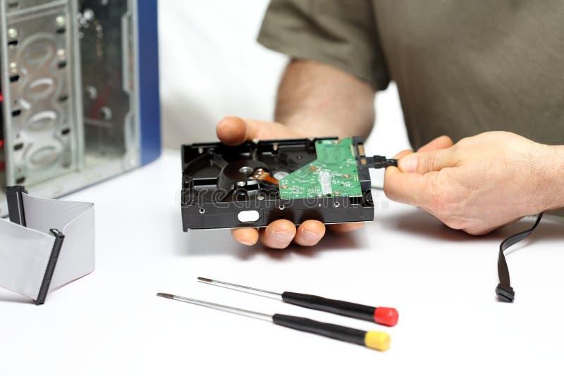 Arbetaren reparerar en dator arkivbild