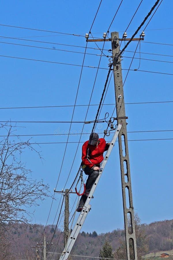 Arbetaren reparerar ledningsnätet på polen, klättring den fäste trappuppgången Arbete på höjd Telefonkabelnät Electrificati arkivfoton