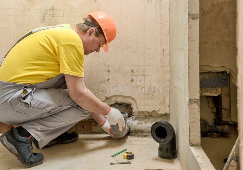 Arbetaren sätter ett kloakavrinningrör arkivfoto