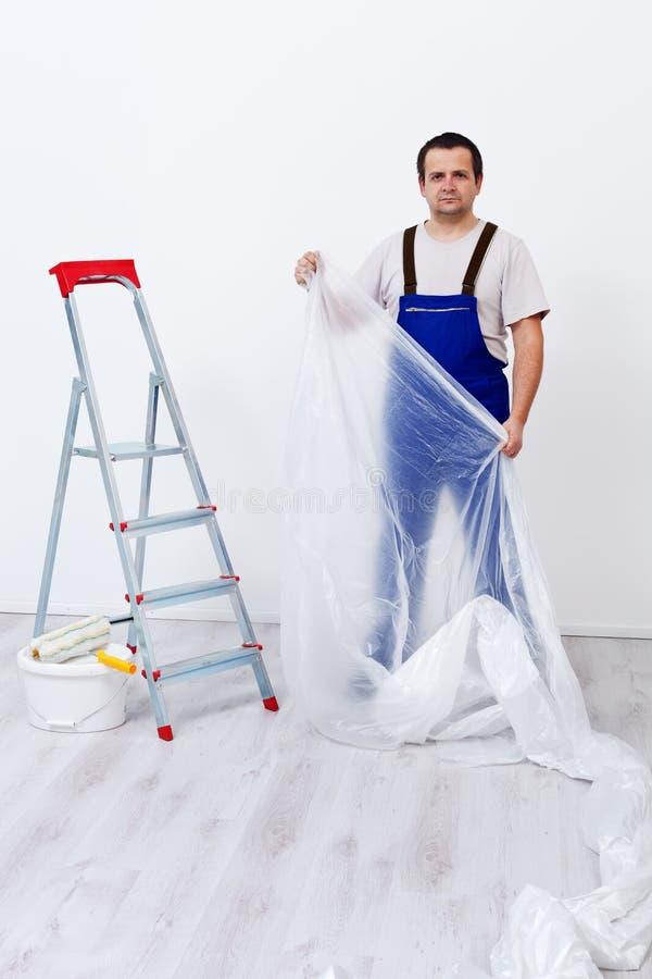 Arbetaren som lägger skydd, filmar, innan han målar arkivfoton
