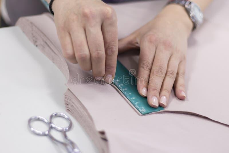 Arbetaren som syr produktion, gör en fläck på detaljerna av snittet royaltyfri bild