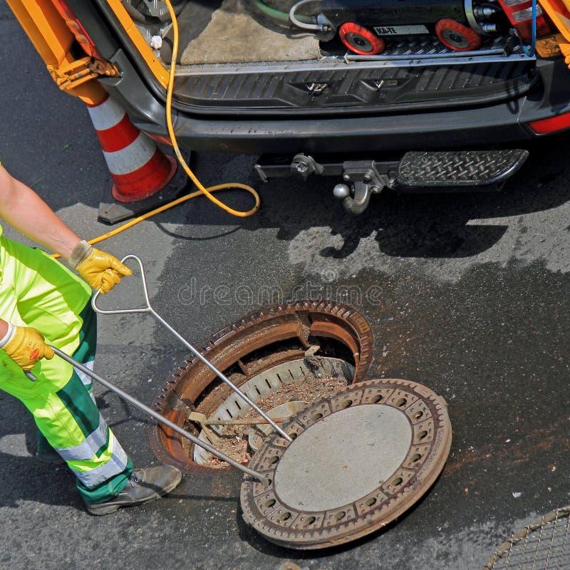 Arbetaren stänger en manhålräkning i gatan arkivbilder