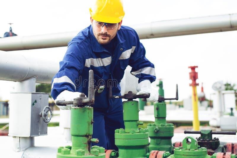 Arbetaren stänger ventilen på den olje- rörledningen arkivbilder