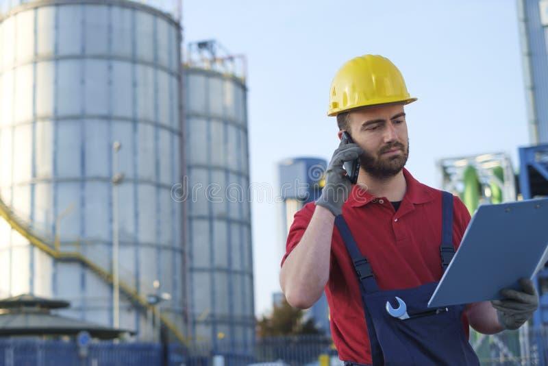 Arbetaren utanför arbeta för fabrik klädde med säkerhetsoveraller royaltyfria bilder