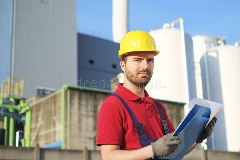 Arbetaren utanför arbeta för fabrik klädde med säkerhetsoveraller e royaltyfri fotografi