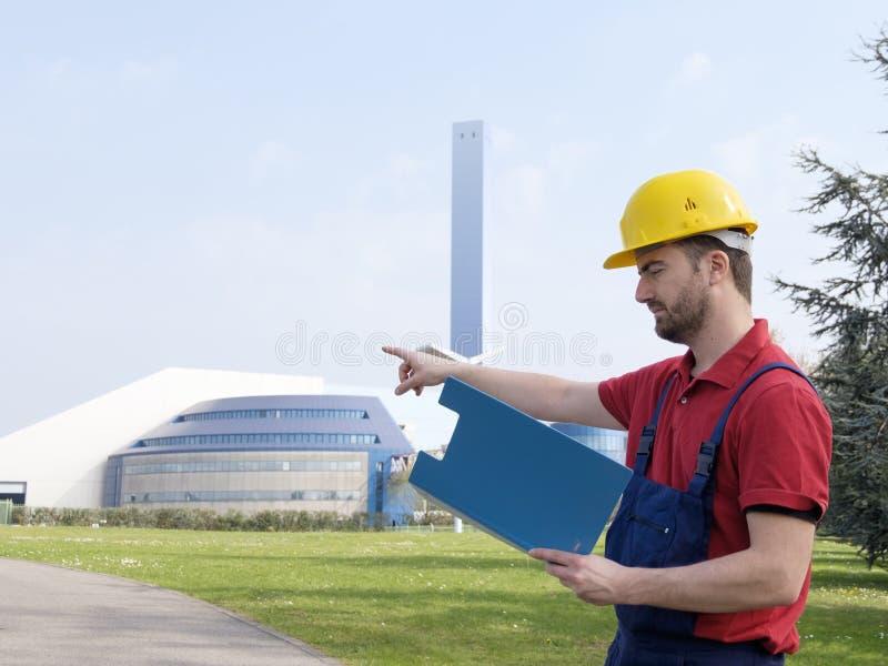 Arbetaren utanför arbeta för fabrik klädde med säkerhetsoverallutrustning fotografering för bildbyråer