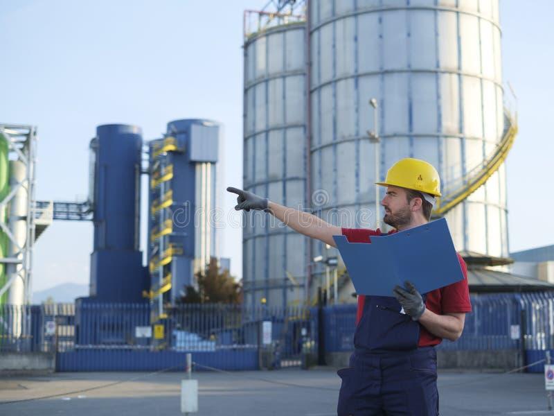Arbetaren utanför arbeta för fabrik klädde med säkerhetsoverallutrustning arkivfoto