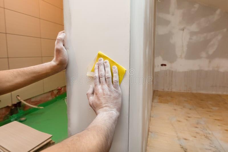 Arbetarhänder troweling vid sandpapper som rumväggen i en lägenhet är inderkonstruktion som omdanar, renovering arkivfoto