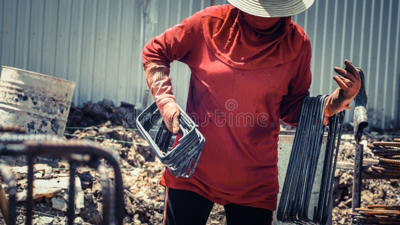 Arbetarhåll som blandar stål för rund stång på tankeskapelsehållen som blandar stål för rund stång på konstruktionsplatsen för vä royaltyfri foto