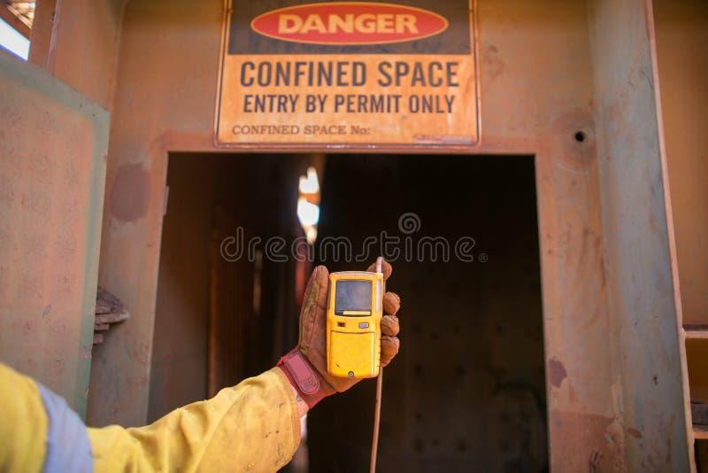 Arbetarhand som rymmer apparaten f?r gasprovdirekt?r, medan b?rja s?kerhetsgas som testar atmosf?r p? uppslagsordet och utg?ngen  arkivbild