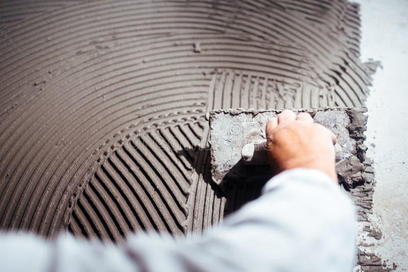 Arbetarhand som tillfogar bindemedel för installation för keramiska tegelplattor royaltyfri foto