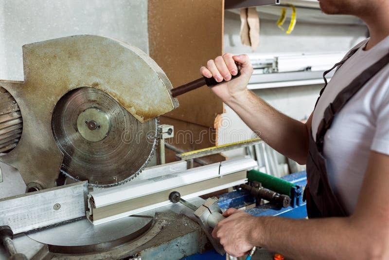 ArbetarklippPVC profilerar med cirkelsågen arkivbilder