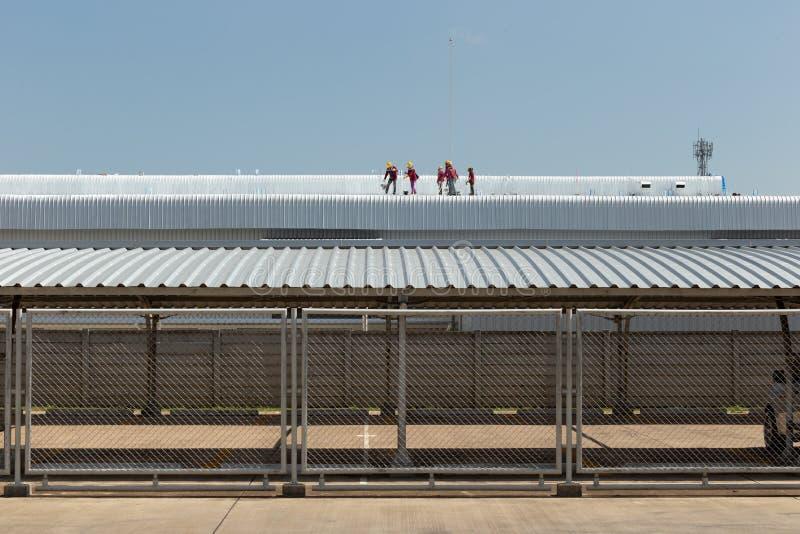 Arbetarmålning på taket av fabriken royaltyfri bild