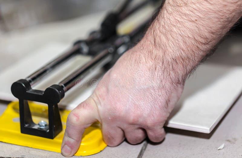 Arbetarmannen klipper den keramiska tegelplattan fotografering för bildbyråer