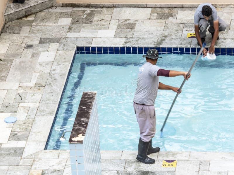 Arbetarmanrengöring en simbassäng i semesterort royaltyfria foton