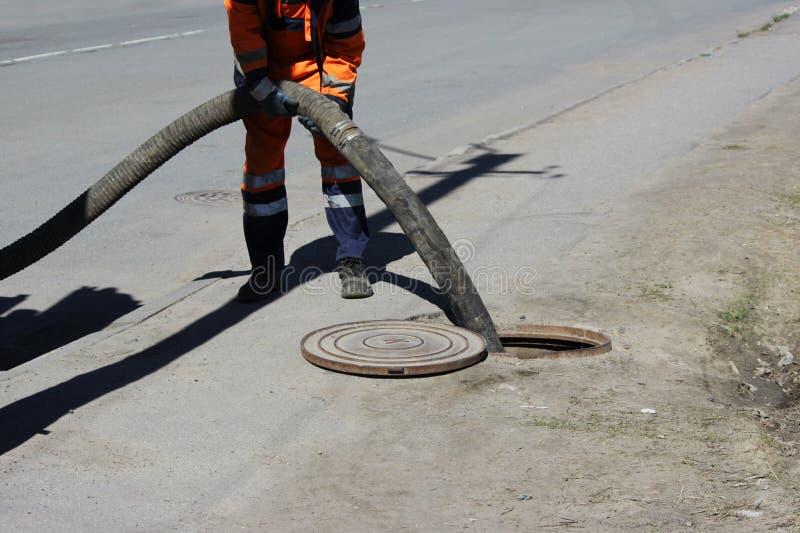 Arbetarossenizatoren pumpade kloak ut ur kloaksystemet till och med luckan i gatan avloppsnätarbetare på renhållning royaltyfri fotografi