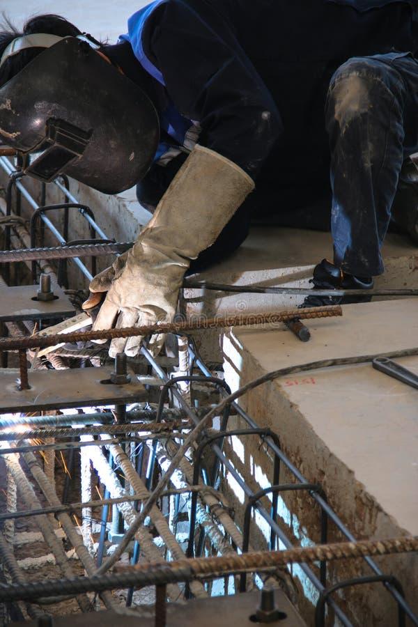 Arbetarsammanträde som gristrar fundamentstrukturen arkivfoton