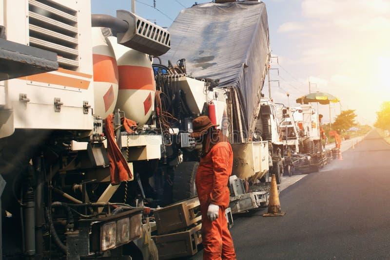 arbetarväg som stenlägger konstruktions- och asfaltmaskiner arkivbild