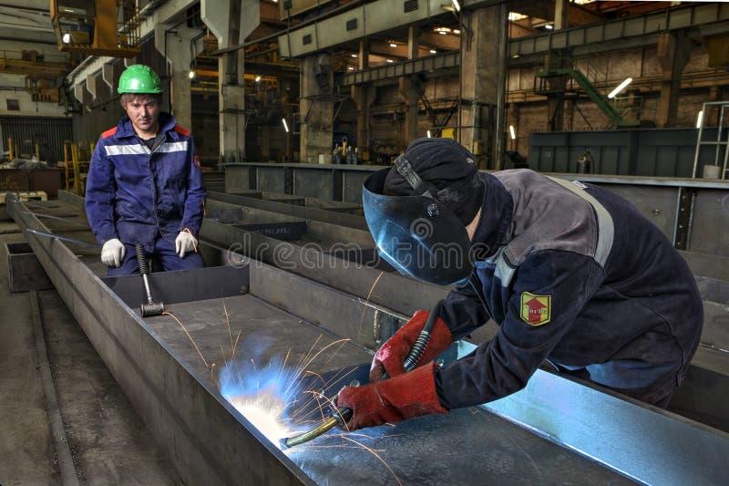 Arbetarwelderen svetsar manuellt stålark genom att använda gasfacklan, MIG fotografering för bildbyråer