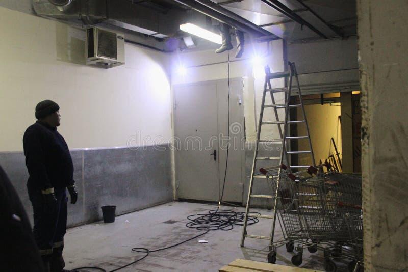 Arbete av industriellt rent av kloak, rörmokeri i byggnaden Två män, specialt medel, trappstegestege royaltyfri bild