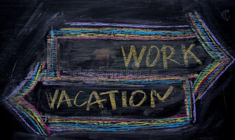 Arbete eller semester som är skriftliga med färgkritabegrepp på svart tavla fotografering för bildbyråer