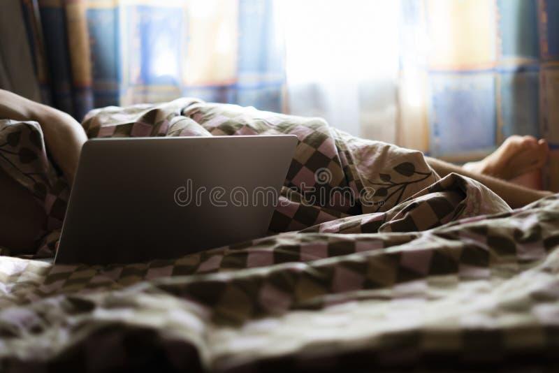 Arbete för övre frilans- manlig website för slut märkes- på en bärbar dator som ligger i säng i morgonen f royaltyfria foton