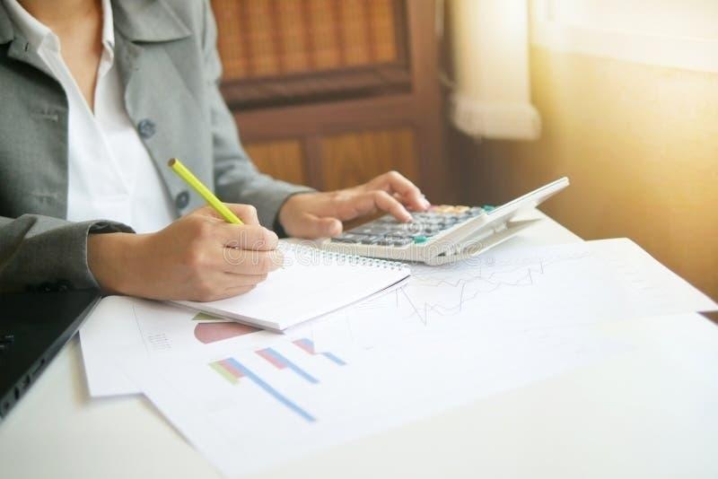 Arbete för analys för finans för anmärkning för handstil för hand för affärskvinna med calc arkivbild
