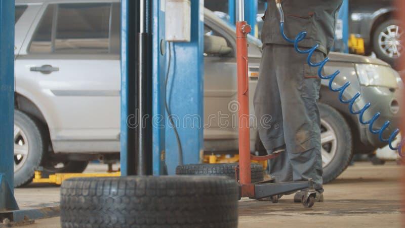 Arbete för bilautomatiskservice - mekaniker under bilen fotografering för bildbyråer