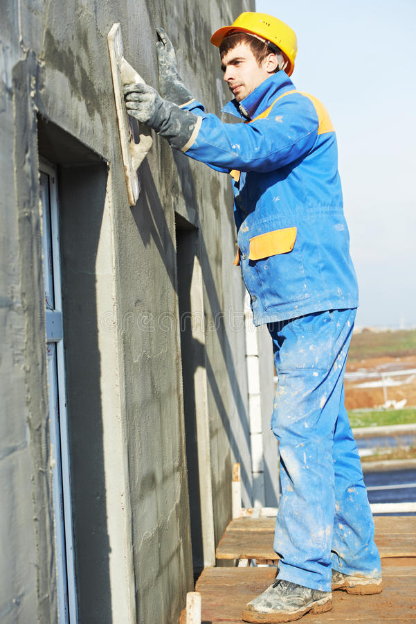 arbete för byggmästarefacadeplasterer royaltyfri foto