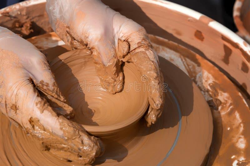 Arbete för händer för keramiker` s med lera på ett hjul för keramiker` s fotografering för bildbyråer
