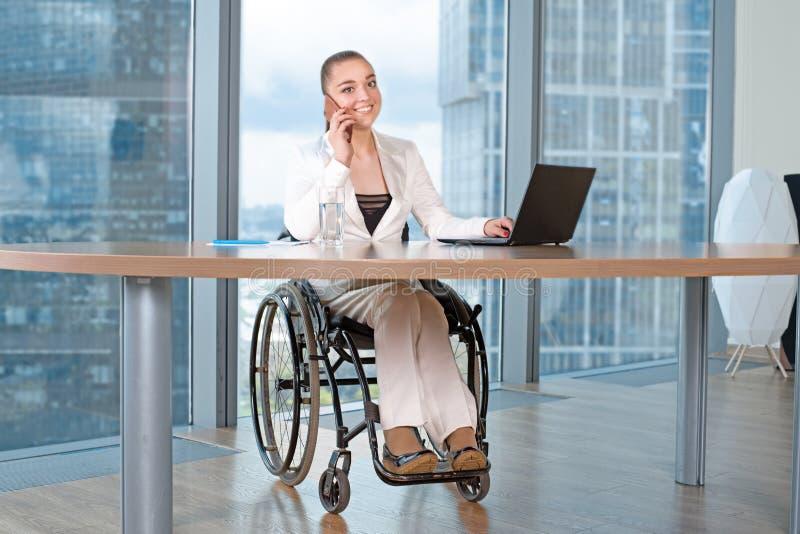 Arbete för rullstol för ogiltig eller rörelsehindrad ung person för affärskvinna sittande i regeringsställning på en bärbar dator royaltyfri bild