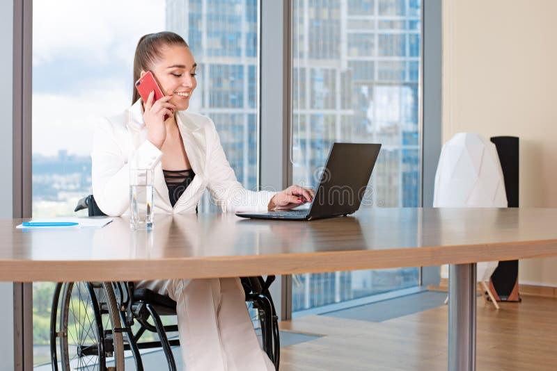 Arbete för rullstol för ogiltig eller rörelsehindrad ung person för affärskvinna sittande i regeringsställning på en bärbar dator arkivfoto