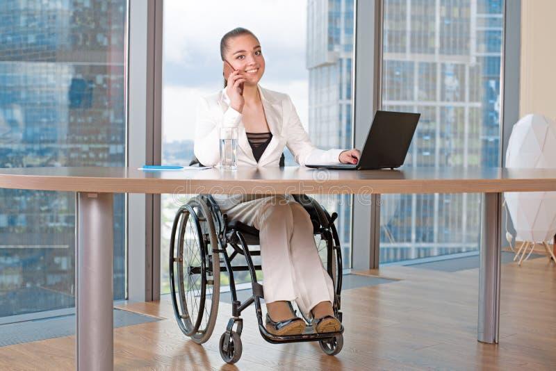 Arbete för rullstol för ogiltig eller rörelsehindrad ung person för affärskvinna sittande i regeringsställning på en bärbar dator arkivbild