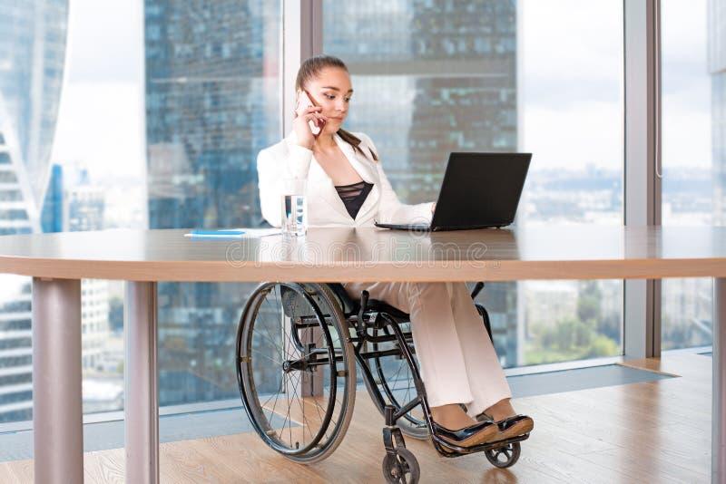 Arbete för rullstol för ogiltig eller rörelsehindrad ung person för affärskvinna sittande i regeringsställning på en bärbar dator royaltyfria foton
