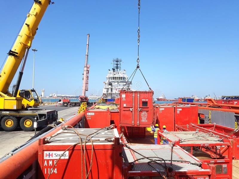 Arbete för skyttel för tillförsel för lastoperationer pågående onboard för fossila bränslenbransch En kustkran lyfter en behållar royaltyfri fotografi