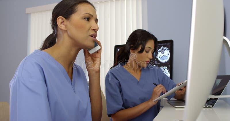 Arbete för två kvinnligt medicinska personaler som ett lag som använder modern teknologi royaltyfri foto